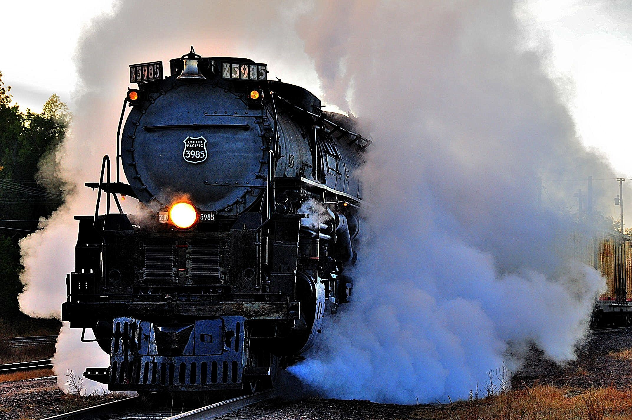 Train engine with a large cloud of smoke/steam coming from the train